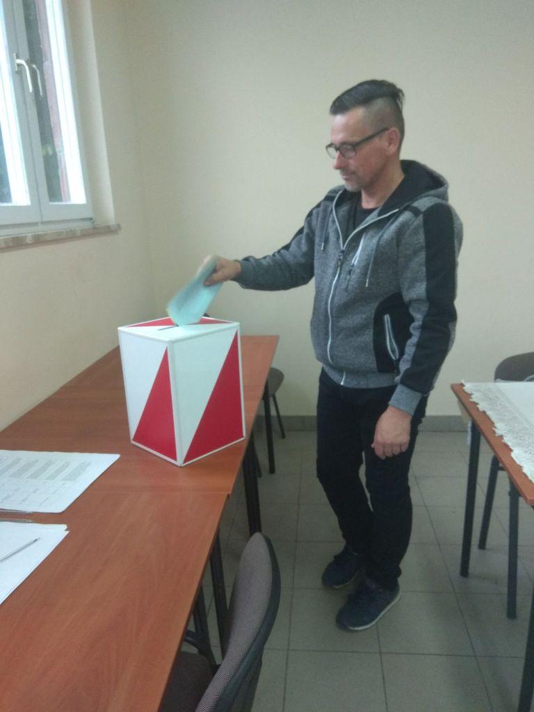 Jeden z glosujących wrzucający kartę do urny