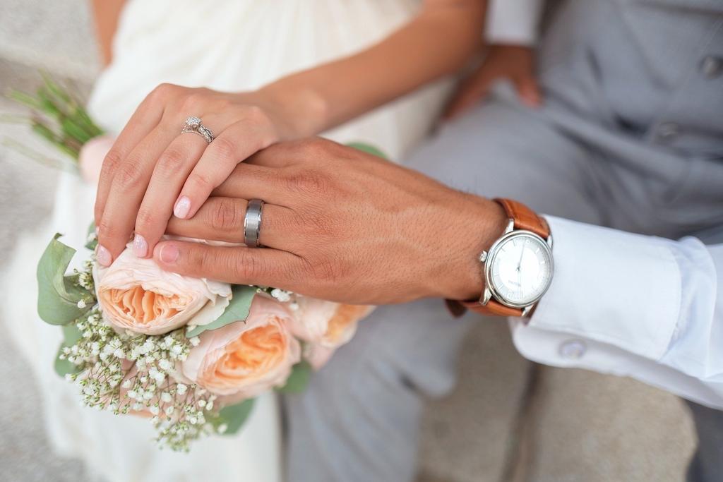 obejmujące się dłonie nowożeńców z bukietem kwiatów