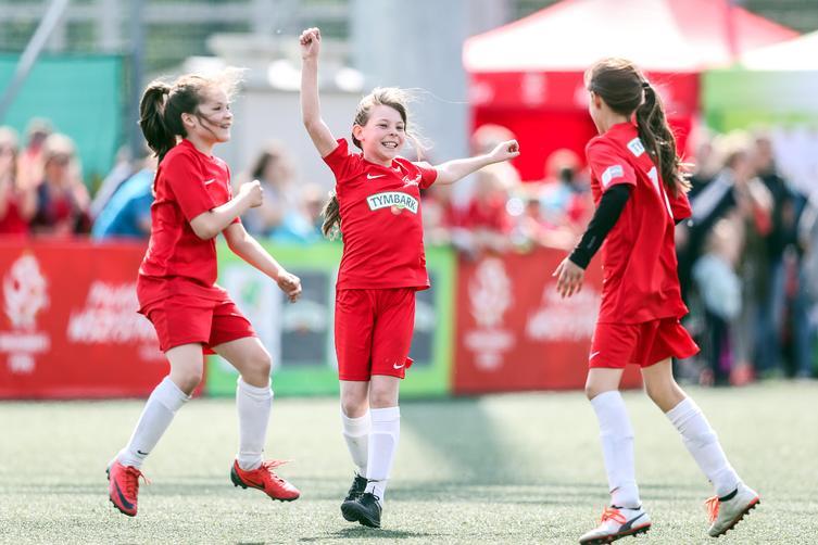Cieszące się dzieci w strojach sportowych z logo Tymbarku