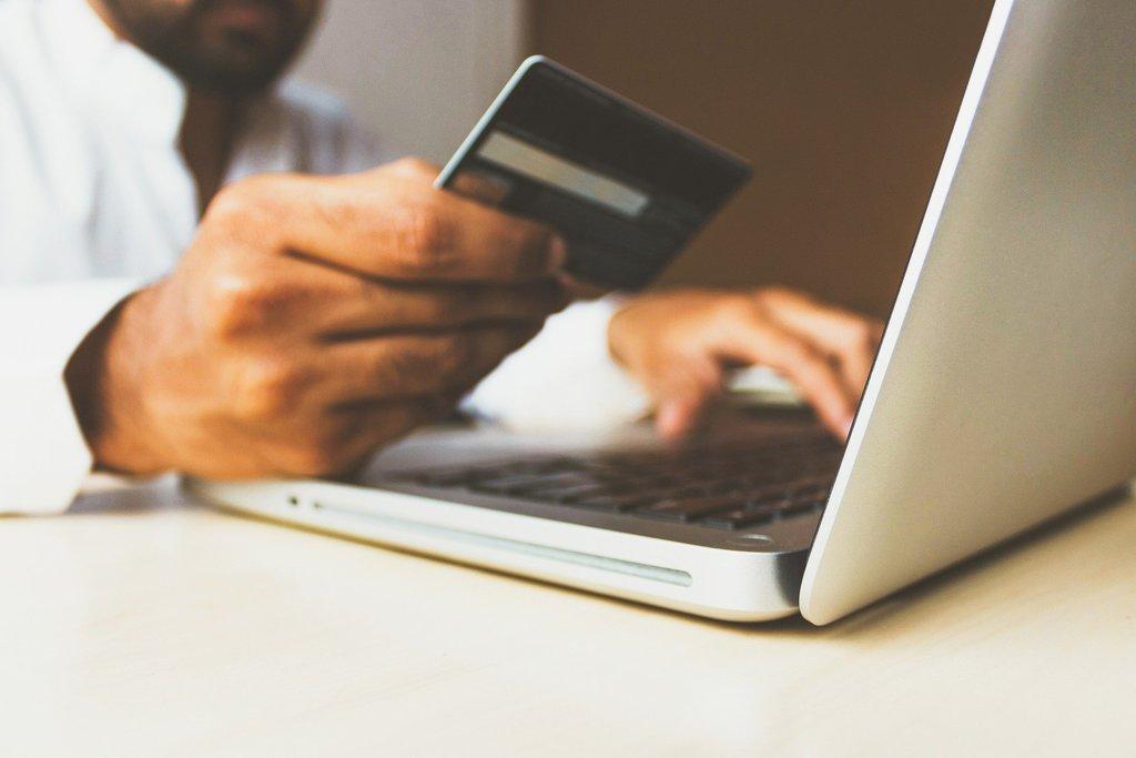 zdjęcie przedstawiające laptop i rękę trzymającą kartę płatniczą