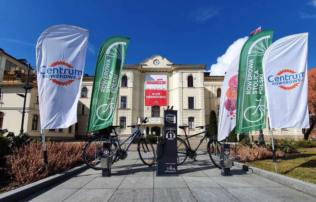 Rowery i inne nagrody w rywalizacji miast, banery sponsora centrumrowrwe.pl na tle Budynku Urzędu Miasta Bydgoszcz