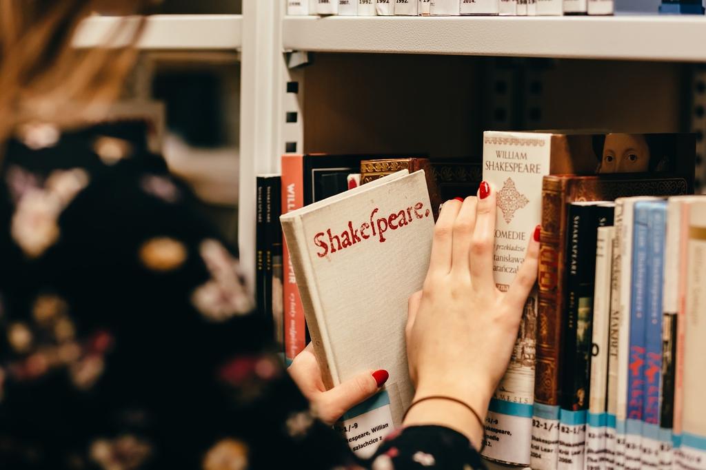 Zdjęcie przedstawiające kobietę sięgającą po książkę.