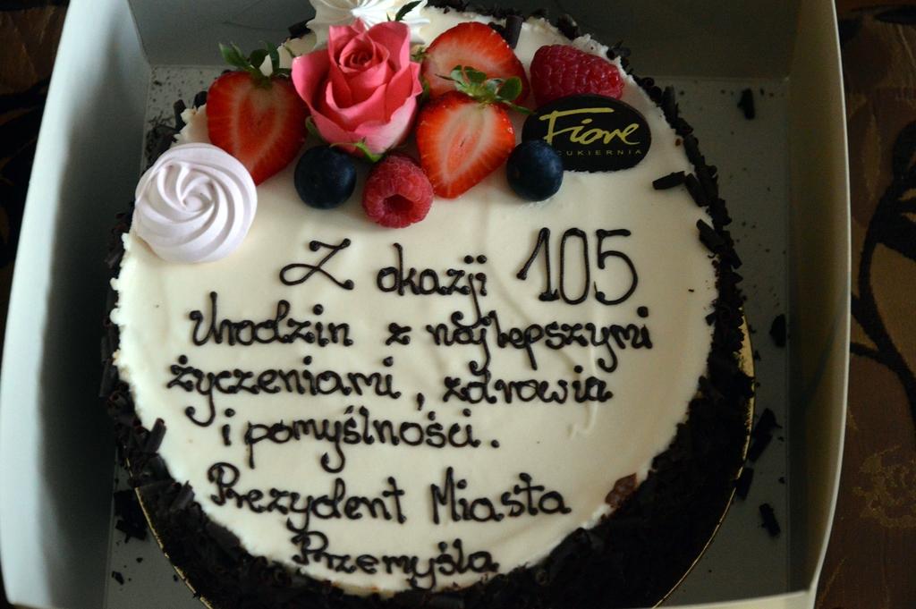 urodzinowy tort z napisem: Z okazji 105. urodzin z najlepszymi życzeniami zdrowia i pomyślności. Prezydent Miasta Przemyśla