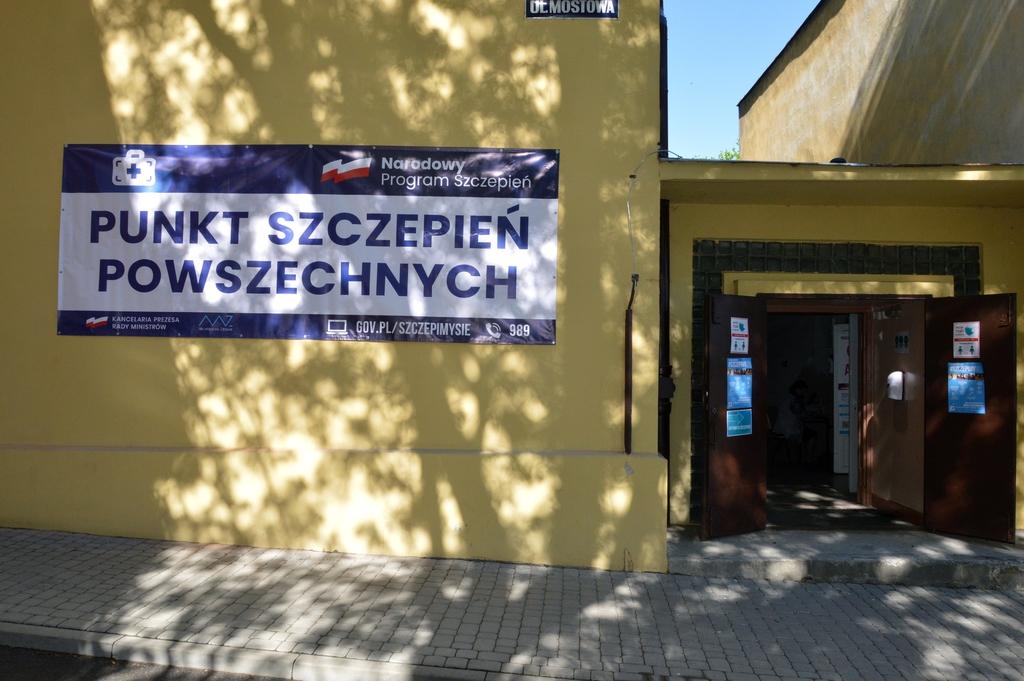 tablica na budynku przed wejściem z napisem Punkt Szczepień Powszechnych