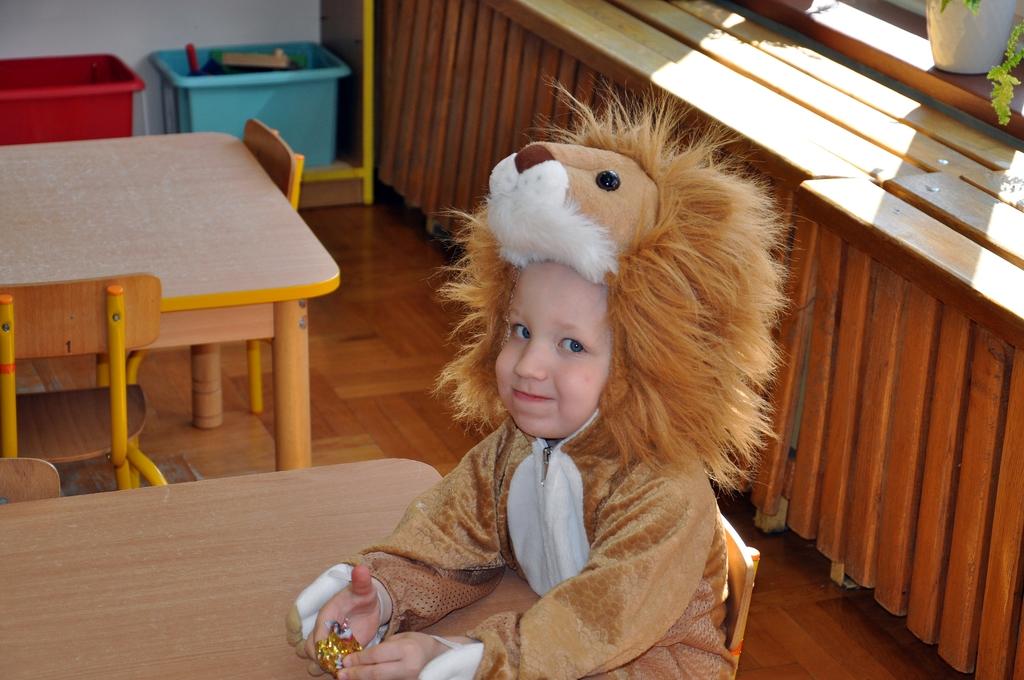 chłopiec w stroju lwa siedzący przy stoliku