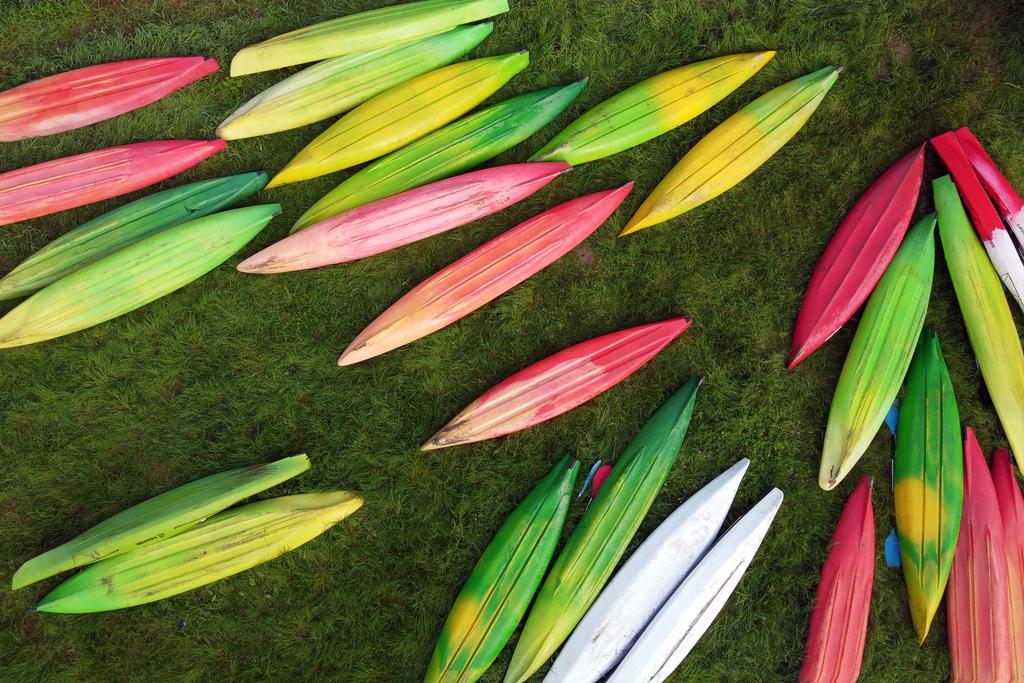 kolorowe kajaki obrócone dnem do góry na brzegu Sanu