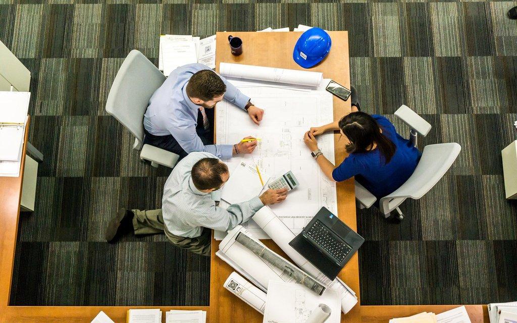 spotkanie biznesowe - trójka ludzi przy biurku nad dokumentami