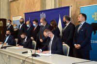 Podpisanie umowy- Prezydent Wojciech Bakun, Minister Cieślak i Wiceprezes KZN Sroka. Za stołem prezydialnym stoją pozostali uczestnicy spotkania