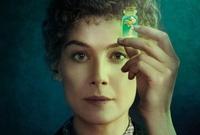"""Fragment plakatu filmu """"Skłodowska"""". Twarz aktorki i uniesiona ręka z fiolką"""