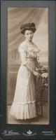 Jedno ze zdjęć z wystawy - sylwetka kobiety w białej sukni przy stoliku z podpisem B. Henner, ul. Mickiewicza 6