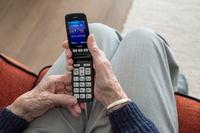 starszy człowiek trzyma w dłoniach telefon komórkowy.jpeg