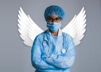 zdjęcie lekarki w niebieskim kitlu i maseczce na twarzy z białymi, anielskimi skrzydłami