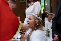 Zdjęcie przedstawiające dziewczynkę przyjmującą I Komunię Świętą.