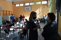 Dyrektor Szpitala Barbara Stawarz udziela wywiadu. w tle osoby oczekujące na szczepienia