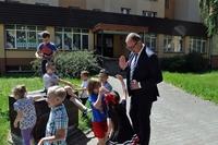 Prezydent z grupą dzieci na placu przed przedszkolem