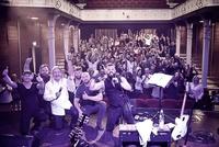 Wspólne zdjęcie zespołu DOC i Marka Piekarczyka razem z publicznością na sali widowiskowej Zamku