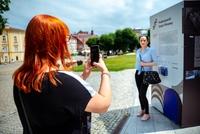 Uczestnicy wycieczki szlakiem filmowym przy standzie reklamującym szlak