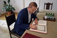 Rafał Paśko wpisuje się do księgi pamiątkowej
