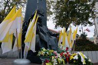 Pomnik papieża Jana Pawła II udekorowany flagami papieskimi ze złożoną przez samorząd wiązanką kwiatów